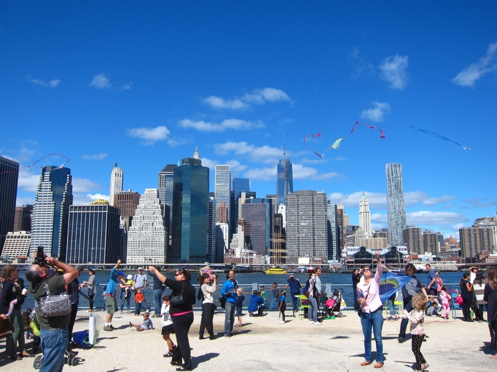 kite day in the park in dumbo, with a great view of downtown manhattan in the background