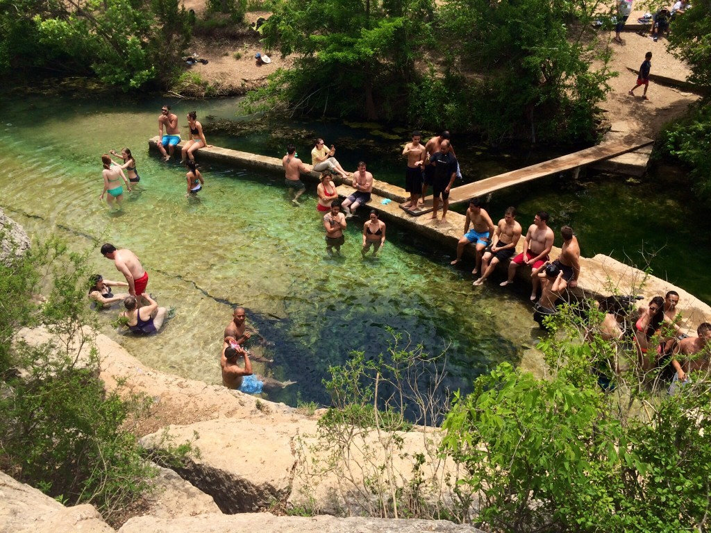 the scene at jacob's well in wimberley, texas (the dark circle in the water is the 30-foot well)