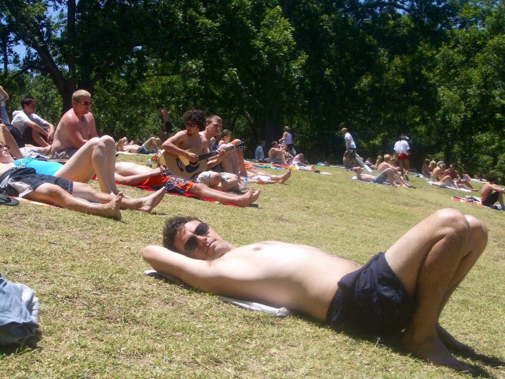sun bathing at austin's barton springs, with a token guitar player in the background