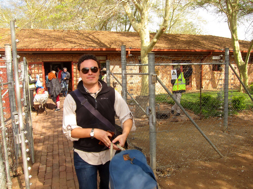 "my husband with his carry-on duffle after passing through ""security"" at the hoedspruit airport."