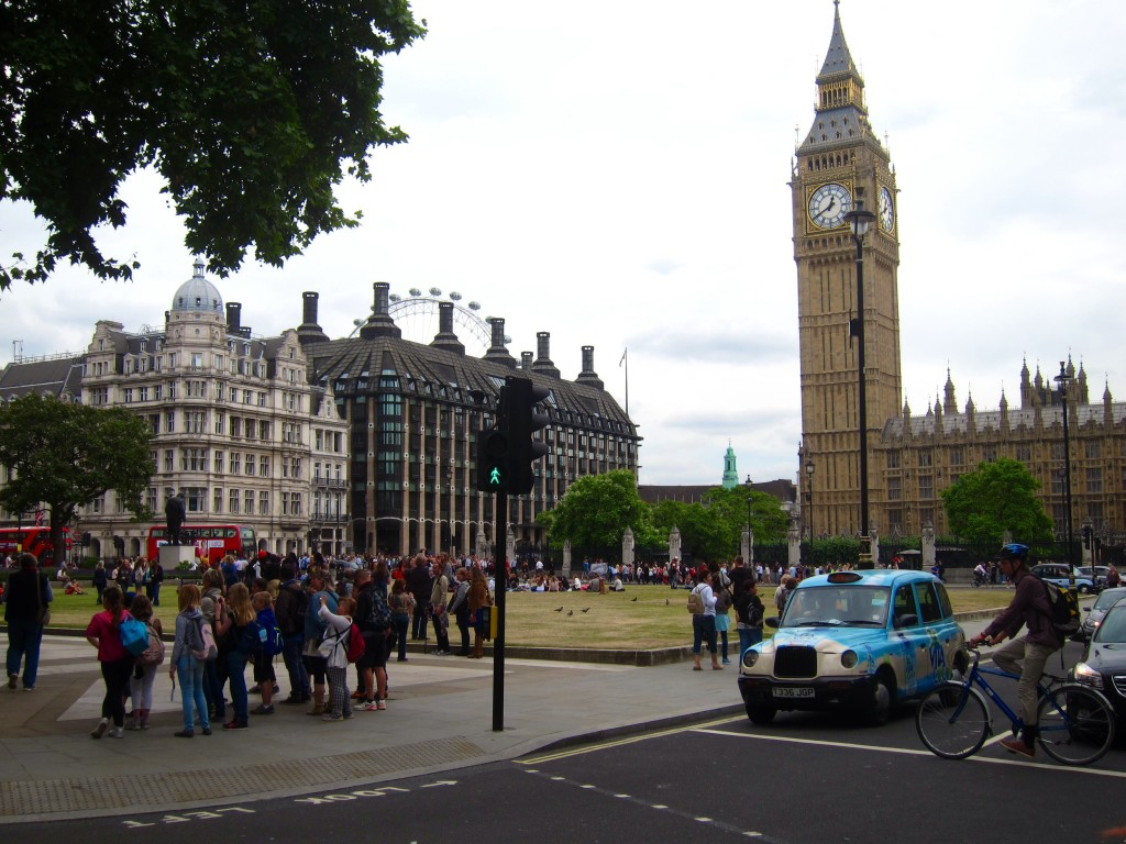 the scene in westminster: tourists, cabbies, big ben, and the london eye keeping watch in the background